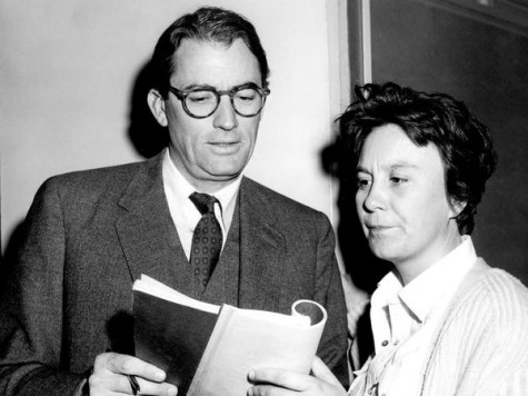 Harper Lee, right, looks over her book To Kill a Mockingbird, with the star of the film, actor Gregory Peck, in 1962.