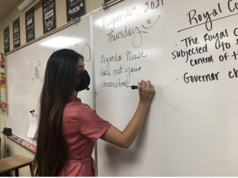 Ms. Yaquelin Montiel, once reading these whiteboards at CHS, is now writing on one in preparation for her students.
