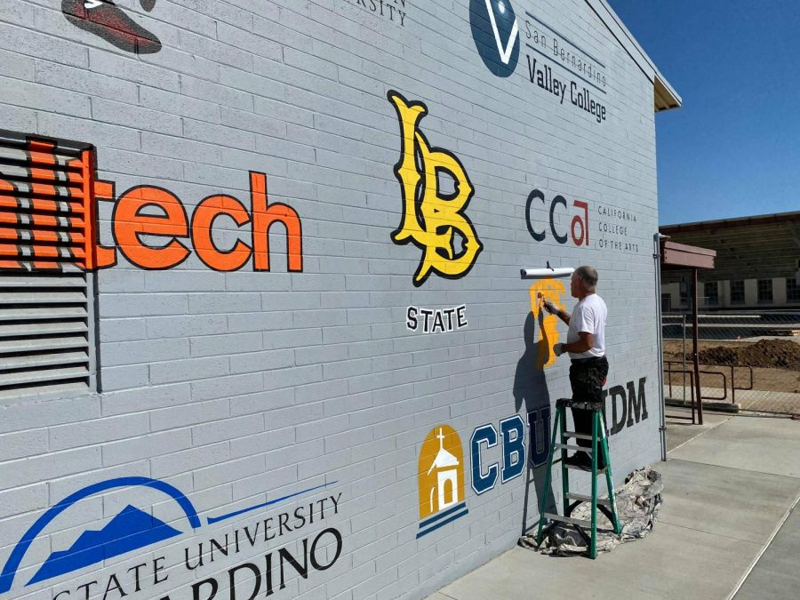 Tom Seibert of Murals for Schools adds the USC Trojan logo to the college mural on DC Lane.
