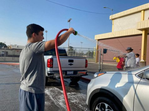 Cross-Country Assistant Coach Isaac Duran hoses down a car during todays 3rd annual Car Wash Fundraiser.