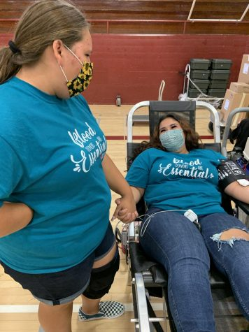Larissa Lopez (Grade 11), HEAL student and 2nd blood donor of the day, laughs as friend Haley Arenas supports her while getting blood drawn.