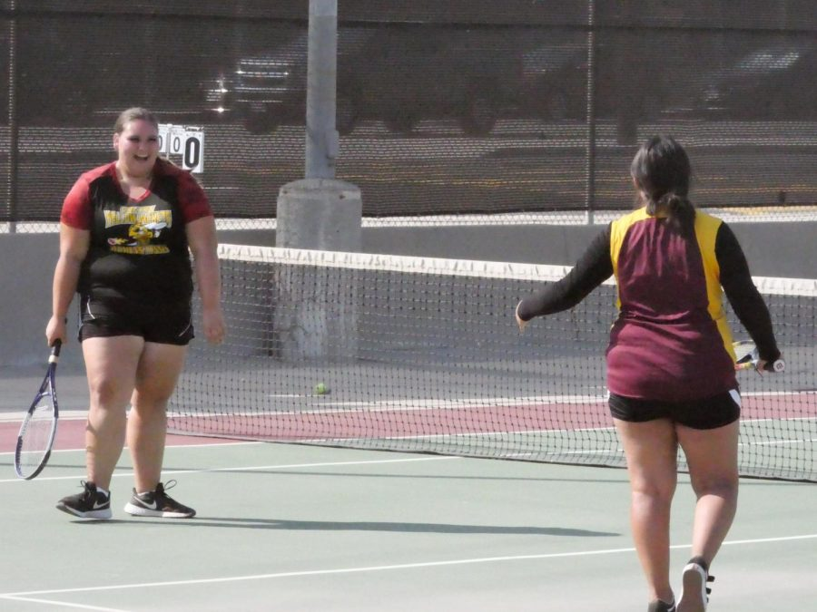 Junior Hailey Arenas (left) and her doubles teammate Jamie Santos (right) celebrate after scoring a point against Liberty High.