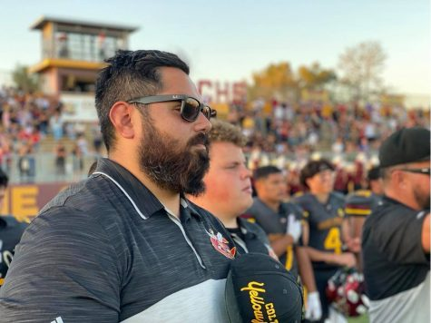 Coach Ray Rodriguez stands in salute during the presentation of colors before Colton took the field against Bloomington High on August 27.